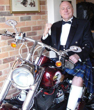 MC and entertainer Keith King from England sitting astride a Harley Davidson motorcycle, dressed in the Italian National Tartan